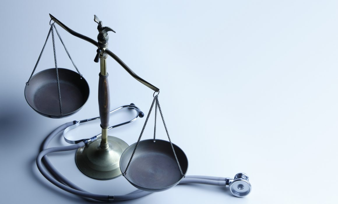 Stethoscope lying at the base of a scale of justice